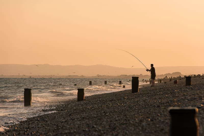 Silhouette of man fishing on the beach
